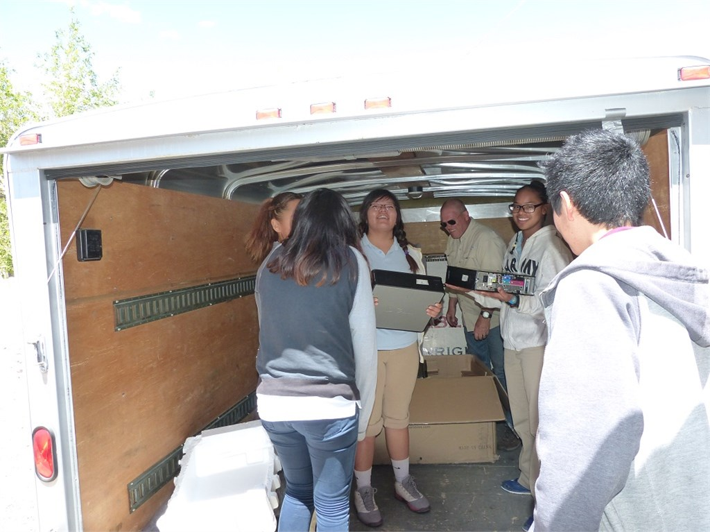 Native American Christian Academy students helping Randy unload twenty refurbished computers to update their computer lab.